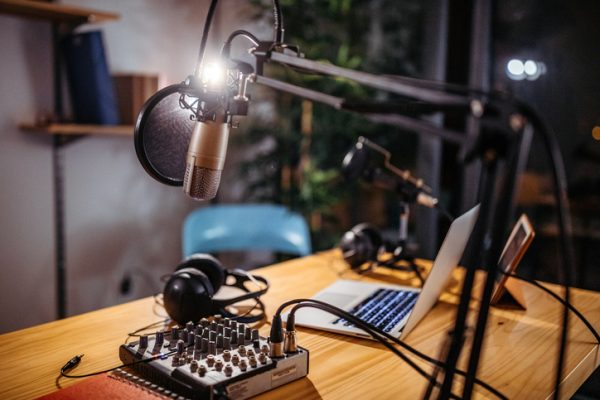 picture of a podcast studio with microphones, sound mixer and laptop